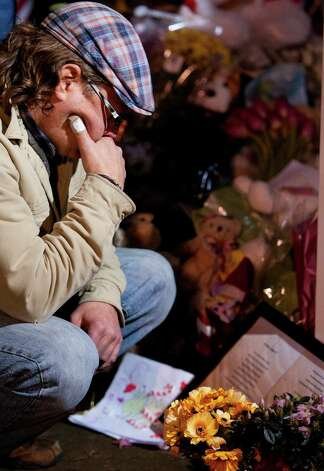 A man looks at an inscription at a memorial site Thursday, December 20, 2012 in Newtown, Conn., honoring the individuals who were killed during a shooting at Sandy Hook Elementary School last Friday. The school was evacuated after Adam Lanza opened fire killing 26 individuals, 20 whom were children. Photo: Cody Duty, Cody Duty/Hearst Newspapers / The News-Times