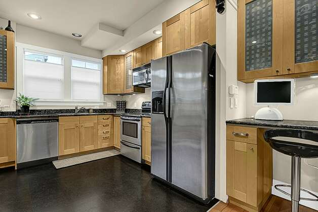 Kitchen of 2005 23rd Ave. W. The 2,810-square-foot house, built in 1909, has four bedrooms, 2.25 bathrooms, vaulted ceilings, period fixtures, radiators, an enclosed porch, a family room, a patio and a two-car garage on a 3,675-square-foot lot. It's listed for $629,000. Photo: Courtesy Redfin