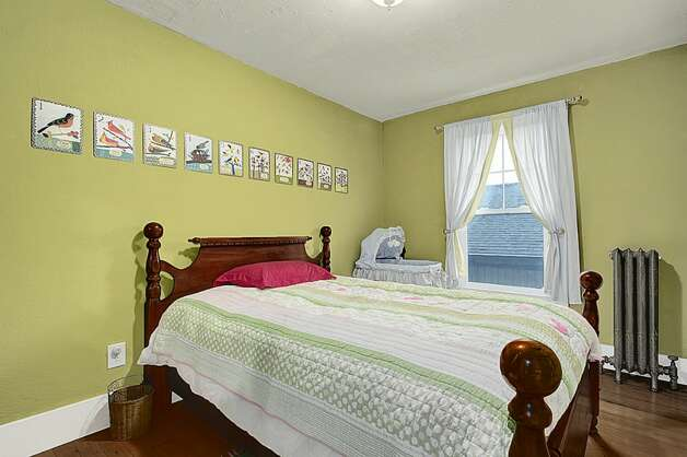 Bedroom of 2005 23rd Ave. W. The 2,810-square-foot house, built in 1909, has four bedrooms, 2.25 bathrooms, vaulted ceilings, period fixtures, radiators, an enclosed porch, a family room, a patio and a two-car garage on a 3,675-square-foot lot. It's listed for $629,000. Photo: Courtesy Redfin