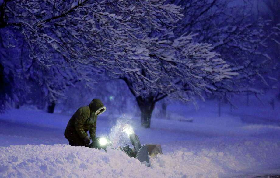 A local resident clears snow from his driveway after an overnight snowfall left many schools and businesses closed for the day, Thursday, Dec. 20, 2012, in Urbandale, Iowa. (AP Photo/Charlie Neibergall) Photo: Charlie Neibergall