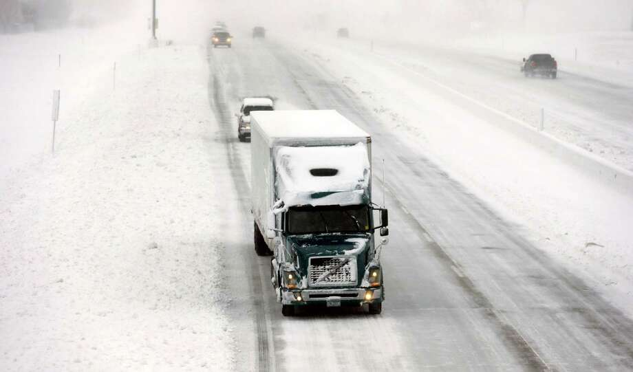 A truck makes its way down a snow covered Interstate I-35/I-80, Thursday, Dec. 20, 2012, in Des Moines, Iowa. The first widespread snowstorm of the season began a slow crawl across the Midwest on Thursday with some areas receiving as much as 15 inches of snow. (AP Photo/Charlie Neibergall) Photo: Charlie Neibergall