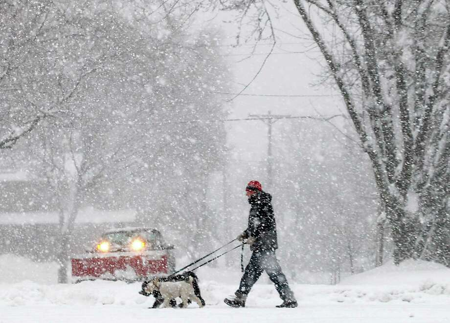 Steve Gordon of Madison, Wis., walks his dogs along Grandview Blvd. on the city's south side as a steady snowfall moves throughout the area Thursday, Dec. 20, 2012. The first major snowstorm of the season began its slow eastward march across the Midwest Thursday, creating treacherous, sometimes deadly driving conditions and threatening to disrupt some of the nation's busiest airports ahead of the holiday weekend. (AP Photo/Wisconsin State Journal, John Hart) Photo: John Hart