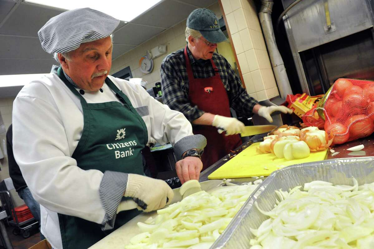 Chris Jones of Feurabush, left, and Bob Headwell of Cambridge cut onions as volunteers prep food for the Christmas Day dinner at the Capital City Rescue Mission Thursday Dec. 20, 2012 in Albany, N.Y. (Lori Van Buren / Times Union)