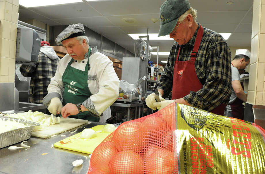 Chris Jones of Feurabush, left, and Bob Headwell of Cambridge cut onions as volunteers prep food for the Christmas Day dinner at the Capital City Rescue Mission Thursday Dec. 20, 2012 in Albany, N.Y. (Lori Van Buren / Times Union) Photo: Lori Van Buren