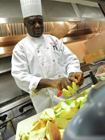 Max Ansong, executive chef for the Rescue Mission, uses an apple slicer to cut apples as volunteers prep food for the Christmas Day dinner at the Capital City Rescue Mission Thursday Dec. 20, 2012 in Albany, N.Y. (Lori Van Buren / Times Union) Photo: Lori Van Buren