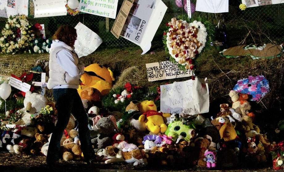 A mourner walks through a memorial site is seen Thursday, December 20, 2012 in Newtown, Conn., honoring the individuals who were killed during a shooting at Sandy Hook Elementary School last Friday. The school was evacuated after Adam Lanza opened fire killing 26 individuals, 20 whom were children. Photo: Cody Duty, Cody Duty/Hearst Newspapers / The News-Times