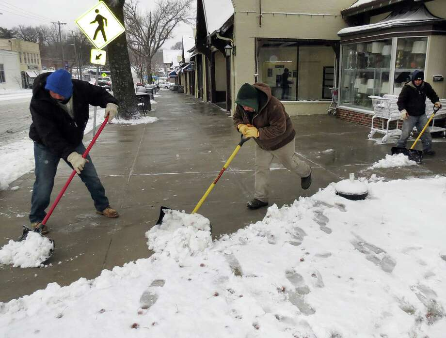 Rosehill Gardens employees Jose Flores, from left, Miguel Villalta and Eddie Urizar clear the sidewalks of the Brookside shops in Kansas City, Missouri, Thursday morning, December 20, 2012, after the overnight snowstorm. Photo: Mary Schulte, McClatchy-Tribune News Service / Kansas City Star