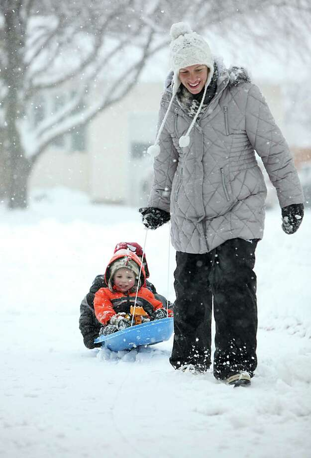Rachel Goins pulls her children, Noah, 2, front, and Caden, 5, in a sled up the driveway during a winter snow storm in Oregon, Wis., Thursday, Dec. 20, 2012.  The first major snowstorm of the season began its slow eastward march across the Midwest early Thursday, creating treacherous driving conditions and threatening to disrupt some of the nation's busiest airports ahead of the holiday weekend. Photo: Amber Arnold, Associated Press / Wisconsin State Journal