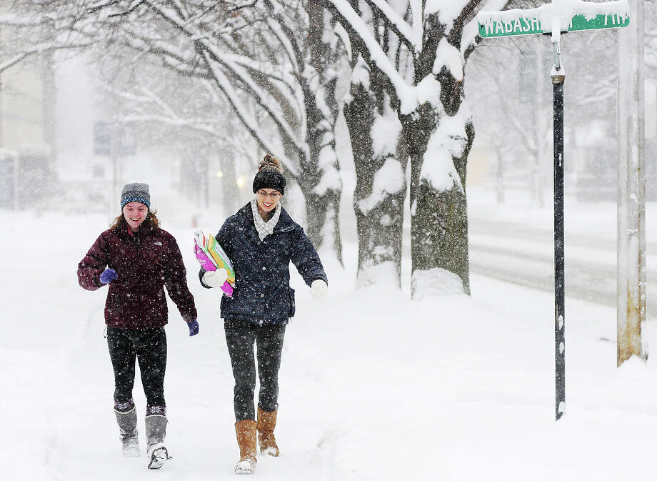 Winona State University students Zoe Reker, left, and Kara Helget walk to the Winona Post Office while it snows Thursday, Dec. 20, 2012, so Helget could return some books in Winona, Minn.  The first major snowstorm of the season began its slow eastward march across the Midwest early Thursday, creating treacherous driving conditions and threatening to disrupt some of the nation's busiest airports ahead of the holiday weekend. Photo: Joe Ahlquist, Associated Press / The Winona Daily News
