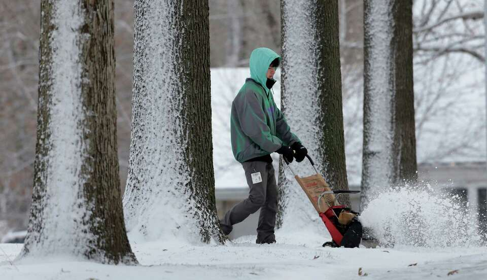 Topher Blunt, of Overland Park, Kan., blows snow off a client's driveway Thursday, Dec. 20, 2012, in