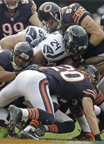 Seattle Seahawks running back Marshawn Lynch (24) is tackled by Chicago Bears safety Craig Steltz (20) and linebacker Brian Urlacher (54) in the first half of an NFL football game in Chicago, Sunday, Dec. 2, 2012. (AP Photo/Kiichiro Sato) Photo: Kiichiro Sato, Associated Press