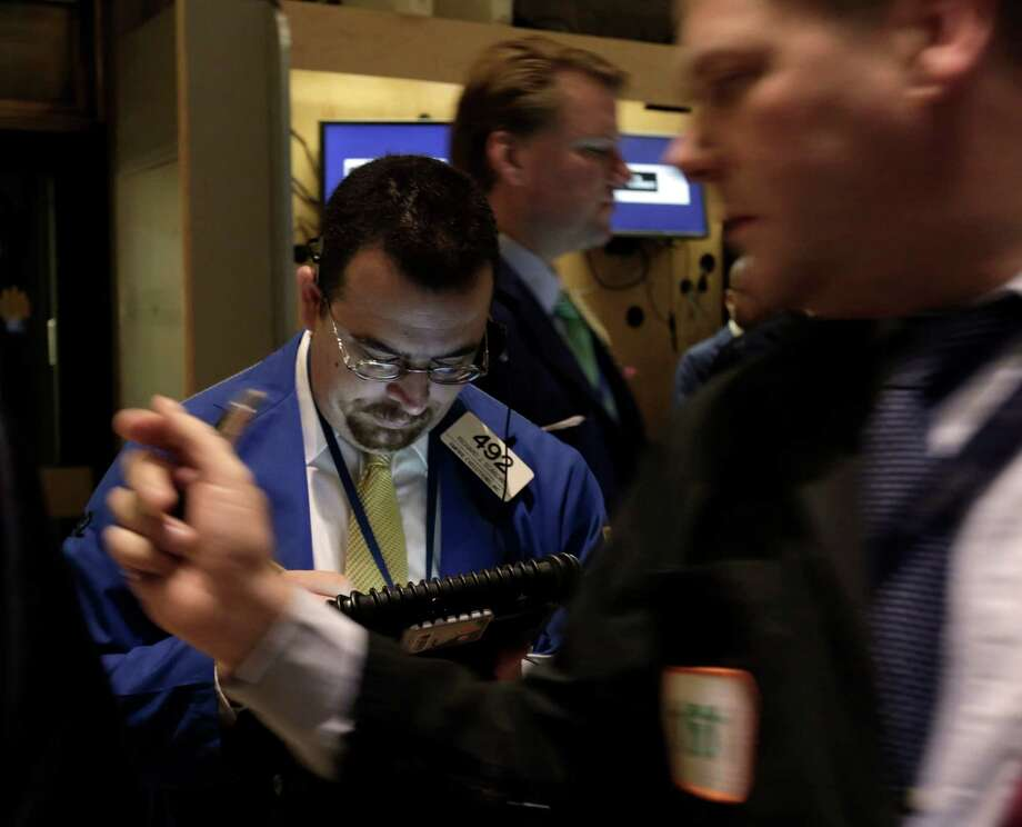 "FILE - Trader Richard Scardino, left, works on the floor of the New York Stock Exchange, in this Dec. 14, 2012 file photo taken in in New York. World stock markets faced resistance Thursday Dec. 20, 2012 after talks turned sour among U.S. political leaders trying to reach an agreement over how to avert an economically disastrous ""fiscal cliff"" before the end of the year. A downturn in U.S. housing starts also hurt sentiment.  (AP Photo/Richard Drew, File) Photo: Richard Drew"