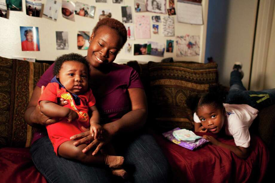 Single parent Twanna Davis sits for a family portrait with her 4-month-old son, Kaleb, and her 3-year-old daughter, Jazzlyn, at their Houston home. Photo: Alyssa Orr, Staff / © 2012 Houston Chronicle