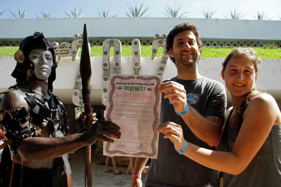 "Capitalism thrives as the world awaits its end. A man dressed as a Mayan ""warrior"" delivers a ""life certificate"" to two lucky tourists in Mexico. The document pays $1 million in case the world ends. Photo: Israel Leal, Associated Press / AP"