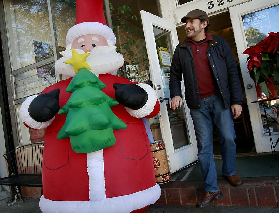 Charlie Harb walks past a large inflatable Santa near the entrance to his Charlie's Cafe in Bernal Heights. Harb was born and raised in Bethlehem, the town famous as the birthplace of Jesus, where his father served as the town Santa. Photo: Brant Ward, The Chronicle