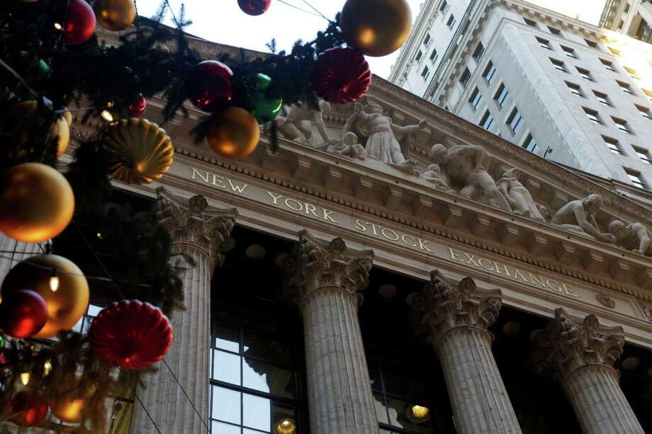 The facade of the New York Stock Exchange is framed by the NYSE holiday tree, Thursday, Dec. 20, 2012. Shares in the company that runs the New York Stock Exchange are surging amid reports that it is in talks to sell itself to a rival stock exchange, Atlanta-based IntercontinentalExchange Inc. (AP Photo/Richard Drew) Photo: Richard Drew