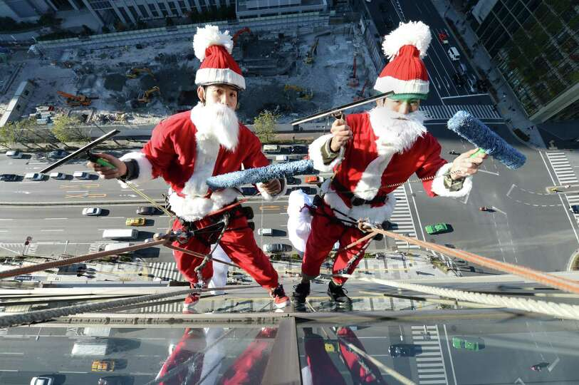 Clad in Santa Claus costumes, workers wipe windows some 55 meters above the ground outside a hotel i