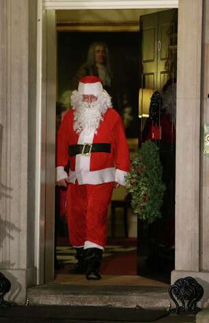 Santa Claus walks out of the front door during a Christmas party hosted for sick children at 10 Downing Street on December 17, 2012 in London, England. Photo: Peter Macdiarmid, Getty Images / 2012 Getty Images