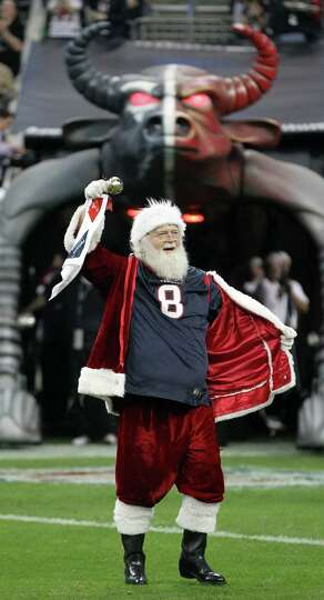 Santa Claus, of the North Pole, shows Houston Texans fans who his favorite team is before the Texans