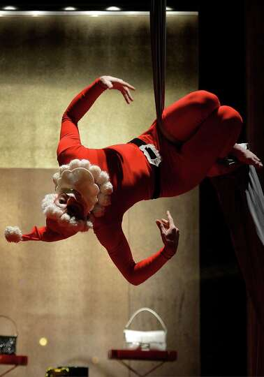 A performer dressed as Santa Claus performs a show during a Christmas sunday shopping in central Rom