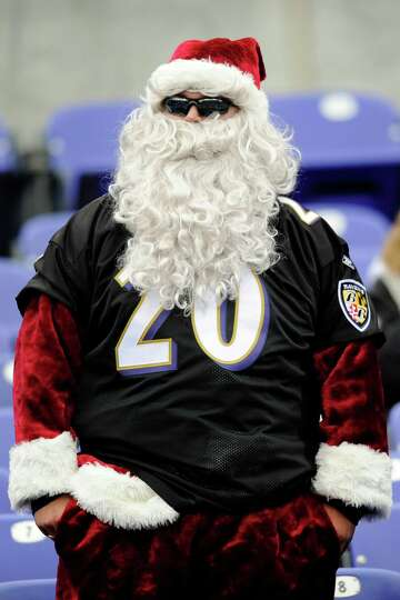A Baltimore Ravens fans dresses as Santa Claus watches his team warm up before an NFL football game