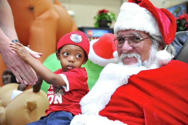 Noah Dixon, 3, keeps a watchful eye on Santa Claus while being lifted away by Officer S. D. Lindsey during the 6th annual Christmas Event for the Children Thursday, December 20, 2012, in Jacksonville, Fla.. Officers from the Jacksonville Sheriff's Office, firefighters from the Jacksonville Fire and Rescue Department as well as other local law enforcement agencies and Fire Scouts went shopping with about a 100 homeless children, from the Sulzbacher Center, for clothes, personal hygiene items and toys. Photo: Bruce Lipsky, Associated Press / Florida Times-Union