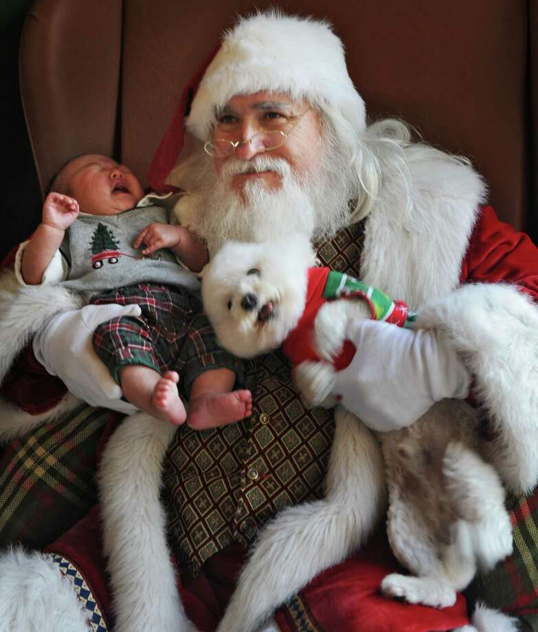 Lance Park, 9-weeks-old, and dog Coco, give Santa a bit of a hard time before finally posing for the keeper photo, Sunday, Dec. 16, 2012, in Jacksonville, Fla.. Pet-owners brought their pets, mostly dogs,  to meet Santa (aka Tom Kiefer) at St. Johns Town Center Mall. Photo: Bob Mack, Associated Press / The Florida Times-Union