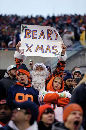 A fan dressed as Santa Claus holds up a signs as Chicago Bears fans watch late in the second half du