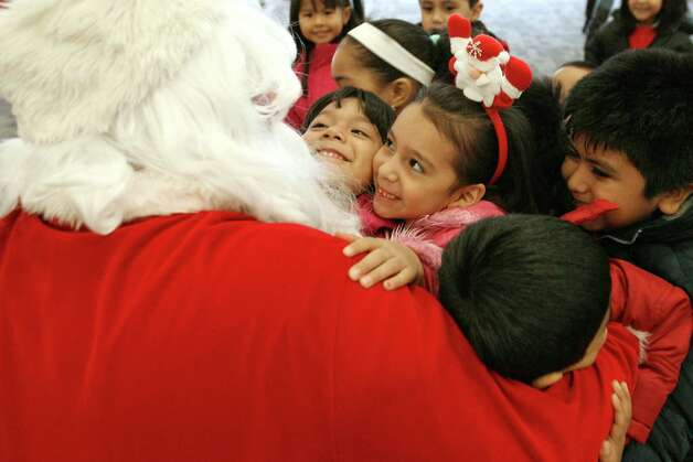 Amy Rosa, center wearing pink and Santa headpiece, and Pre-K classmates at Children's Day Nursery and Family Center in Passaic, N.J, rush to hug Santa as they enter the Expo center in Secaucus, N.J. New Jersey Apartment Association Charitable Fund's 15th Annual Holiday Party to Entertain and Delight More Than 1,000 School Children from Throughout North Jersey at the Meadowlands Expo Center. Photo:  Michael Karas, Associated Press / The Record of Bergen County