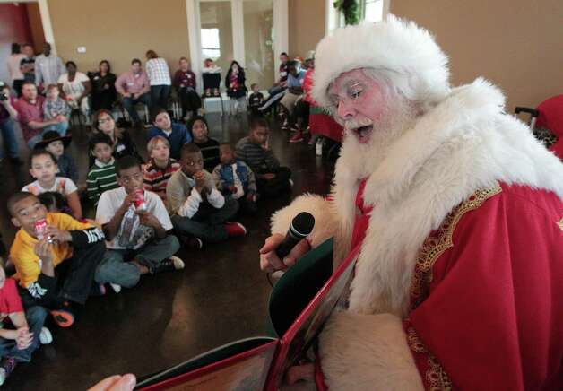 """Santa Claus reads """"Twas the Night Before Christmas"""" during the """"Stuff the Sleigh of Katy"""" Holiday Party for Texas Children's Hospital Pediatric Cancer Patients at The Clubhouse at Firethorne Sunday, Dec. 16, 2012, in Katy. Photo: James Nielsen, Chronicle / © Houston Chronicle 2012"""