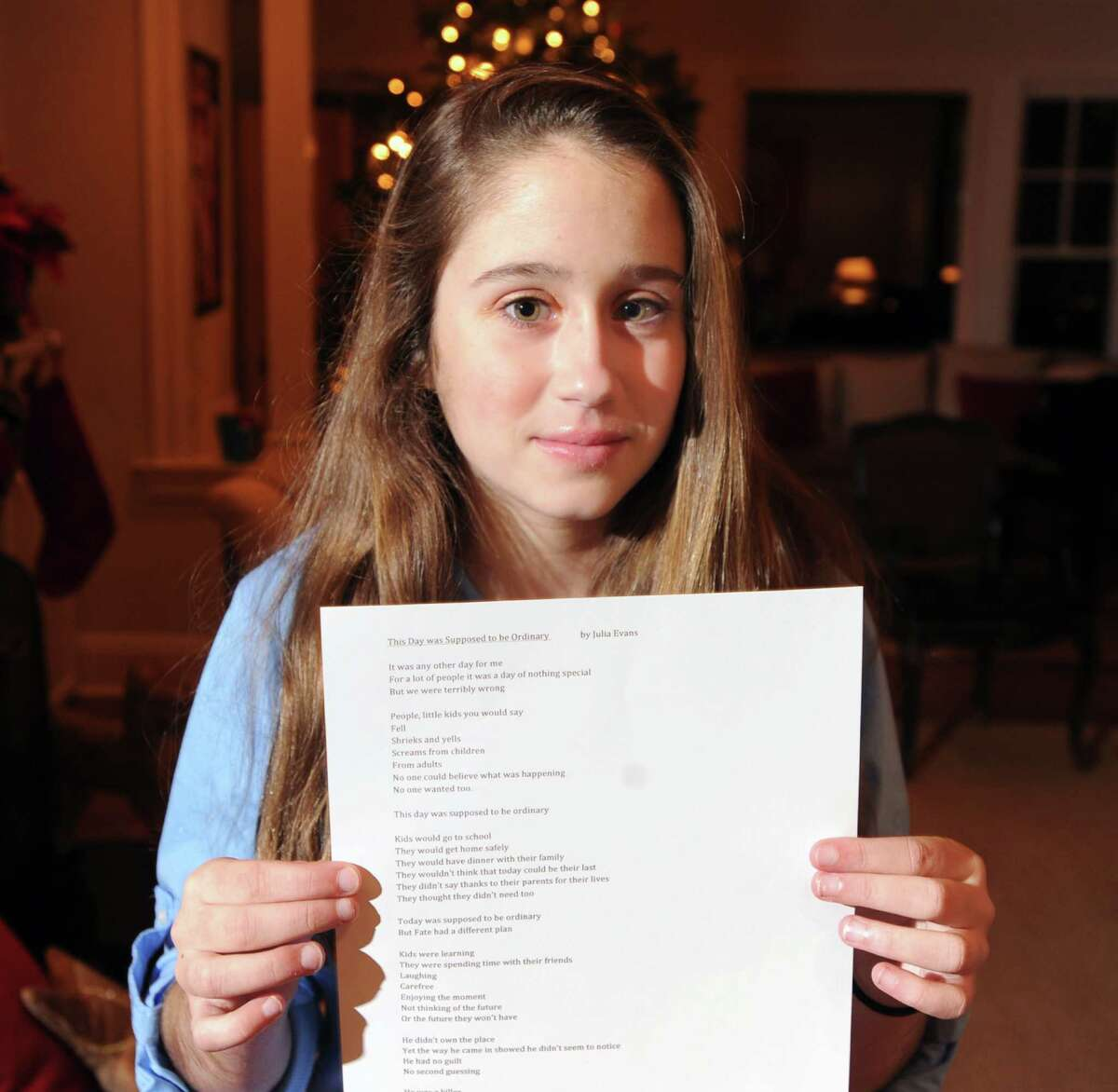 """Julia Evans, 12, of Old Greenwich, holds her poem about the Sandy Hook Elementary School massacre titled """"The Day was Suppose to be Ordinary,"""" at her home, Thursday night, Dec. 20, 2012. Evans is a 7th grader at Greenwich Country Day School."""