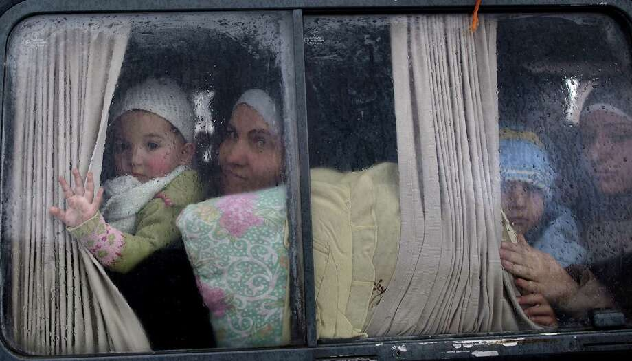 Syrian refugees, who fled their home in Idlib due to a government airstrike, look out of a vehicle's window just after crossing the border from Syria to Turkey, in Cilvegozu, Turkey, Thursday, Dec. 20, 2012. (AP Photo/Muhammed Muheisen) Photo: Muhammed Muheisen