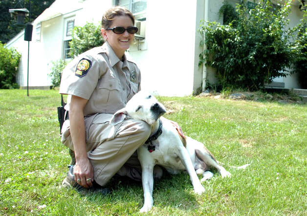 Greenwich Animal Control officer Suzanne Carlin is a leaning post for her adopted Pit Bull Mikey in front of the Animal Control Shelter. Photo: Keelin Daly / Greenwich Time