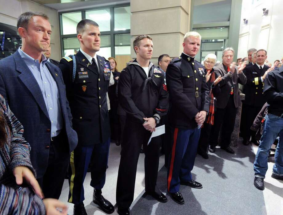 Greenwich natives and servicemen from left, James Waters who served as a Navy Lt., Army Officer Matthew Carstensen,  Jake Isbrandtsen of the Navy and Jake's brother, Marine First Lt. Nick Isbrandtsen, are given a standing ovation during the welcoming home ceremony for servicemen put on by the Greenwich Military Covenant of Care at Greenwich Police Headquarters, Thursday night, Dec. 20, 2012. Photo: Bob Luckey / Greenwich Time