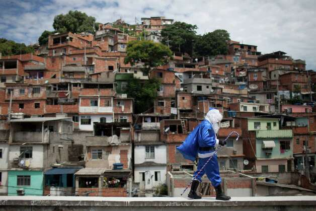A police officer dressed in a Santa Claus costume, with the blue color representing the police, walks in Macacos slum after arriving in a police helicopter in Rio de Janeiro, Brazil, Thursday, Dec. 20, 2012. The Pacifying Police Unit, or UPP, organized for Santa to visit the pacified slum to hand out Christmas gifts to young residents. Photo: Felipe Dana, Associated Press / AP