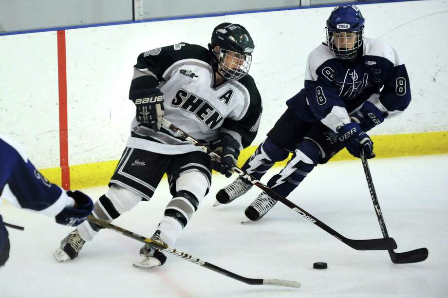 Shenendehowa's Kevin Miles (12), left, and  Saratoga's Nick Winters (8), left, chase a loose puck during their hockey game on Thursday, Dec. 20, 2012, at the Clifton Park Arena in Clifton Park, N.Y. (Cindy Schultz / Times Union) Photo: Cindy Schultz / 00020548A