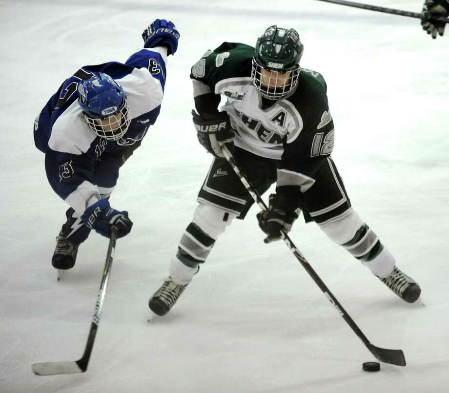 Shenendehowa's Kevin Miles (12), right, looks to shoot as Saratoga's Nick Conchieri (13) defends during their hockey game on Thursday, Dec. 20, 2012, at the Clifton Park Arena in Clifton Park, N.Y. (Cindy Schultz / Times Union) Photo: Cindy Schultz / 00020548A
