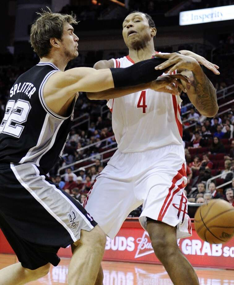 The Spurs' Tiago Splitter (22) knocks the ball away from the Rockets' Greg Smith (4) in the first half on Monday, Dec. 10, 2012, in Houston.