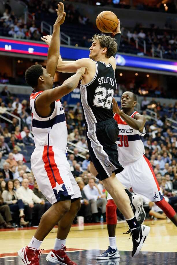 Tiago Splitter (22) of the Spurs puts up a shot in front of Kevin Seraphin (13) and Earl Barron (30) of the Wizards during the second half at Verizon Center on Nov. 26, 2012 in Washington, DC.