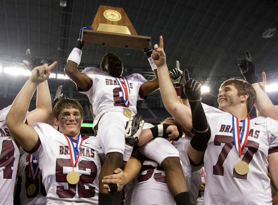 East Bernard's Victor Pettit (9) holds up the championship trophy after defeating Corsicana Mildred 56-14 in the Class 2A Division II state championship at Cowboys Stadium on Thursday, Dec. 20, 2012, in Arlington. Photo: J. Patric Schneider, For The Chronicle / © 2012 Houston Chronicle