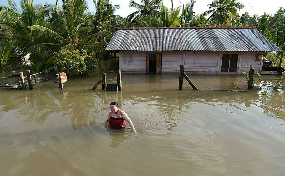 A Sri Lankan flood affected victim wades through a village in the north western province town of Chilaw on December 20, 2012. Flash floods have killed at least 25 people in Sri Lanka and left more than a quarter of a million marooned in their homes, disaster officials said. Heavy rains, which have battered the island for much of the week, were still being reported in 14 of Sri Lanka's 25 administrative districts, with the central highlands -- one of the world's key tea producing regions -- the worst hit. Photo: Ishara S.kodikara, AFP/Getty Images