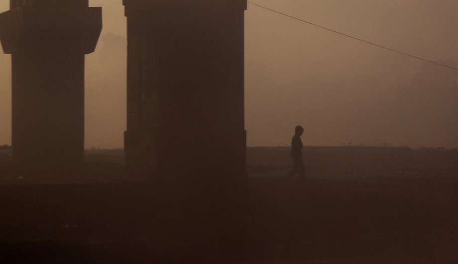 A young Indian boy passes through morning fog on the outskirts of Jammu, India, Thursday, Dec. 20,2012. A cold wave has gripped large parts of northern India. Photo: Channi Anand, Associated Press