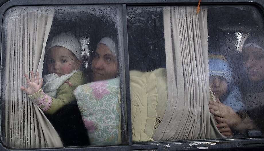 Syrian refugees, who fled their home in Idlib due to a government airstrike, look out of a vehicle's window just after crossing the border from Syria to Turkey, in Cilvegozu, Turkey, Thursday, Dec. 20, 2012. Photo: Muhammed Muheisen, Associated Press