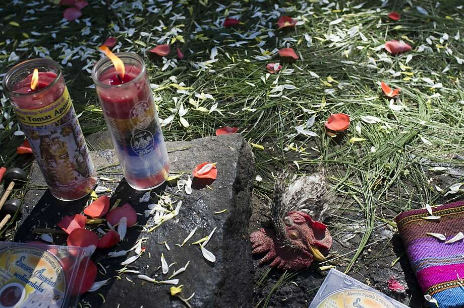 A chicken's head lays on an altar of offerings during a private ceremony at the Iximche archeological site in preparation for the Oxlajuj B'aktun in Tecpan, Guatemala Thursday, Dec. 20, 2012. The Oxlajuj B'aktun is on Dec. 21, marking a new period in the Mayan calendar, an event only comparable in recent times with the new millennium in 2000. While the Mayan calendar cycle has prompted a wave of doomsday speculation across the globe, few in the Mayan heartland believe the world will end on Friday. Photo: Moises Castillo, Associated Press
