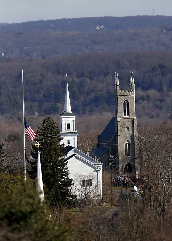A U.S. flag waves at half-staff in front of  Trinity Episcopal Church in Newtown. Photo: Julio Cortez, Associated Press