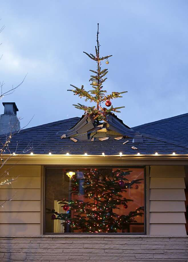 A 14-foot Christmas tree appears to be crashing through the roof of a one-story house, Thursday, Dec. 20, 2012, in Seattle's Magnolia neighborhood. Homeowner Patrick Kruger created the illusion of the tree crashing through the roof by cutting a 14-foot tree into two pieces and attaching the top six-foot section is to a piece of plywood that's bolted to the roof. According to MyNorthwest.com, Kruger, who is an architect, studied the physics of an object breaking through a roof then added sheathing and typical roof construction materials to create the effect. Photo: Elaine Thompson, Associated Press