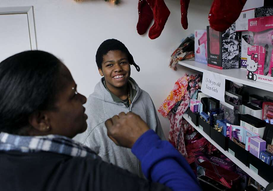 Renado Tims, 13, seeks help from his mom, Annie Wilson, while choosing a gift for his sister at a Salvation Army holiday toy giveaway in San Francisco, Calif. on Thursday, Dec. 20, 2012. Photo: Paul Chinn, The Chronicle