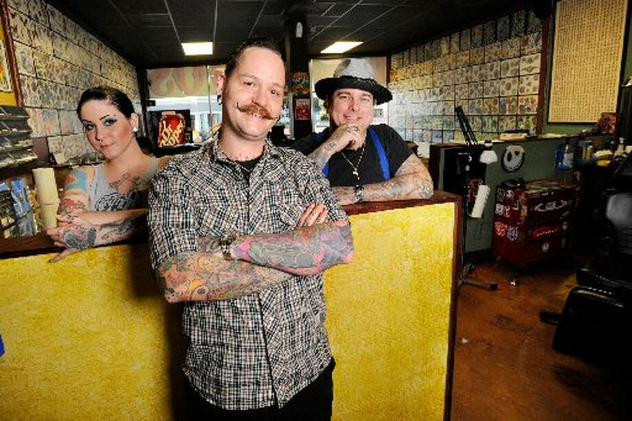 Megan Muzerie, left, tattoo artists Johnny Johno, center, and Shane Monte, right, photographed at Santa Fe Tattoo Parlor located on Calder Avenue. Valentino Mauricio/cat5