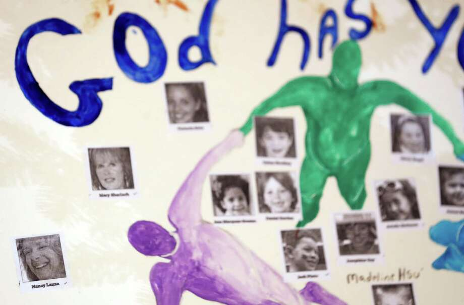 A photograph of Nancy Lanza, bottom left, one of the 27 people allegedly killed by Adam Lanza in the Sandy Hook village of Newtown, Conn., last week, appears on a board at a makeshift memorial, Thursday, Dec. 20, 2012. For the most part, makeshift memorials honor the 26 victims allegedly killed by the gunman, who forced himself into Sandy Hook Elementary School on Dec. 14, 2012. In total, 27 people were killed as officials say Lanza shot and killed his mother, Nancy Lanza, at their home. Nancy Lanza is virtually nonexistent in the memorials. Photo: Julio Cortez