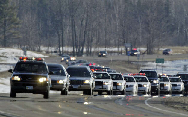 A police motorcade escorts the bodies of Indian police officer Daryl Lussier and his companion Michelle Sigana on their way to the Red Lake Indian Reservation in Red Lake, Minn., Thursday, March 24, 2005.  Jeff Weise, a 16-year-old student at Red Lake High School shot his grandfather Daryl Lussier and his grandfather's companion Michelle Sigana along with seven others and himself on Monday. Officer Lussier's vehicle leads the procession. Photo: MORRY GASH, AP / AP